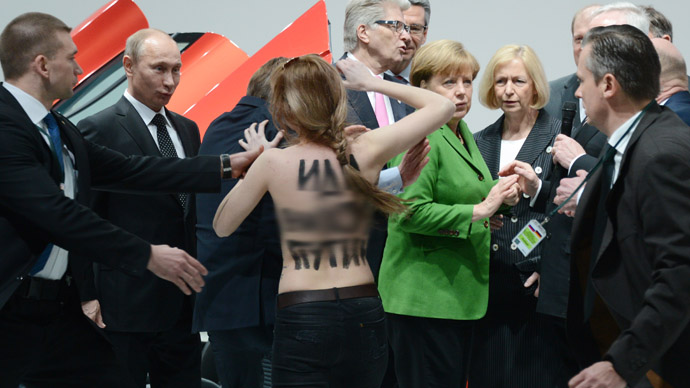 """A topless demonstrator with a message on her back walks towards Russian President Vladimir Putin (L) and German Chancellor Angela Merkel (C) during their visit of the Hanover industrial Fair in Hanover, central Germany, on April 8, 213. Four bare-breated demonstrators shouted """"fuck dictator""""at Russian President Vladimir Putin as he was visiting the Volkswagen stand.   AFP PHOTO / Jochen Lьbke +++ GERMANY OUT"""