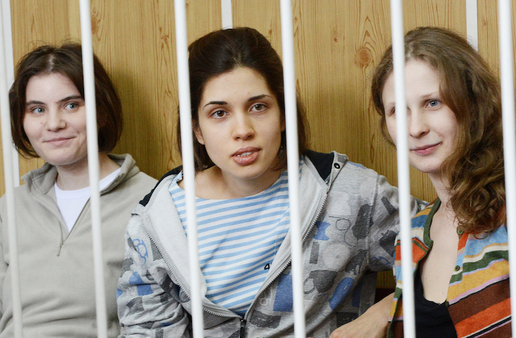 """(FILES) A file picture taken on July 20, 2012 shows members of the all-girl punk band """"Pussy Riot"""" Nadezhda Tolokonnikova (C), Maria Alyokhina (R) and Yekaterina Samutsevich (L), sitting behind bars during a court hearing in Moscow. Prosecutors asked a Moscow court to lock up members of the Pussy Riot girl band for three years after they called for Vladimir Putin's ouster in a song, prompting Madonna to plead for clemency. As the full hearings in the controversial trial went into a second week, the state prosecutor said the young women's crime was so severe they needed to be isolated from society.  AFP PHOTO / NATALIA KOLESNIKOVA        (Photo credit should read NATALIA KOLESNIKOVA/AFP/GettyImages)"""