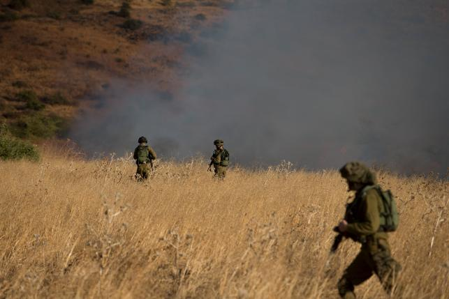 Israeli soldiers patrol next to smoke from a fire caused by a rocket attack in northern Israel, near the Lebanese border, August 20, 2015. REUTERS/JINIPIX