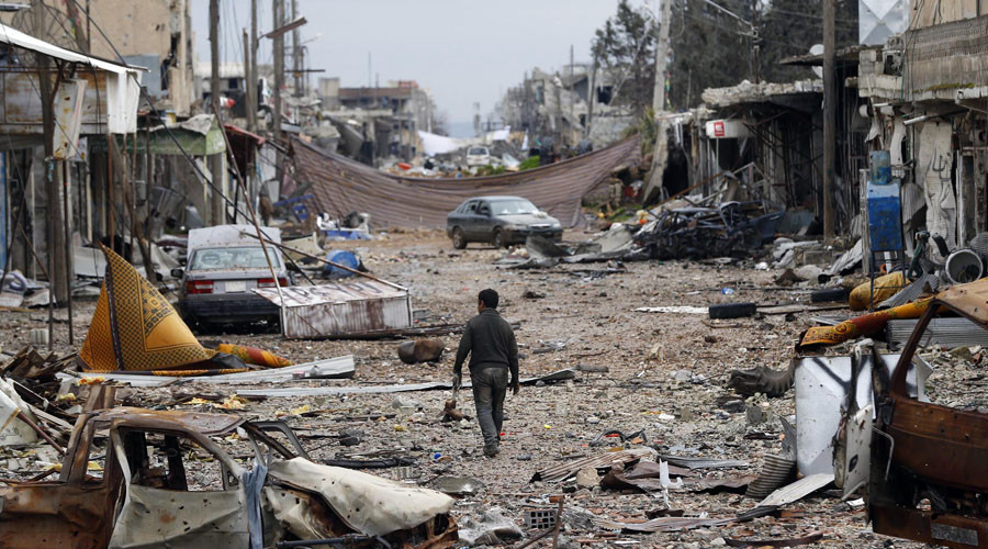 A man walks in a street with abandoned vehicles and damaged buildings in the northern Syrian town of Kobani. © Osman Orsal / Reuters