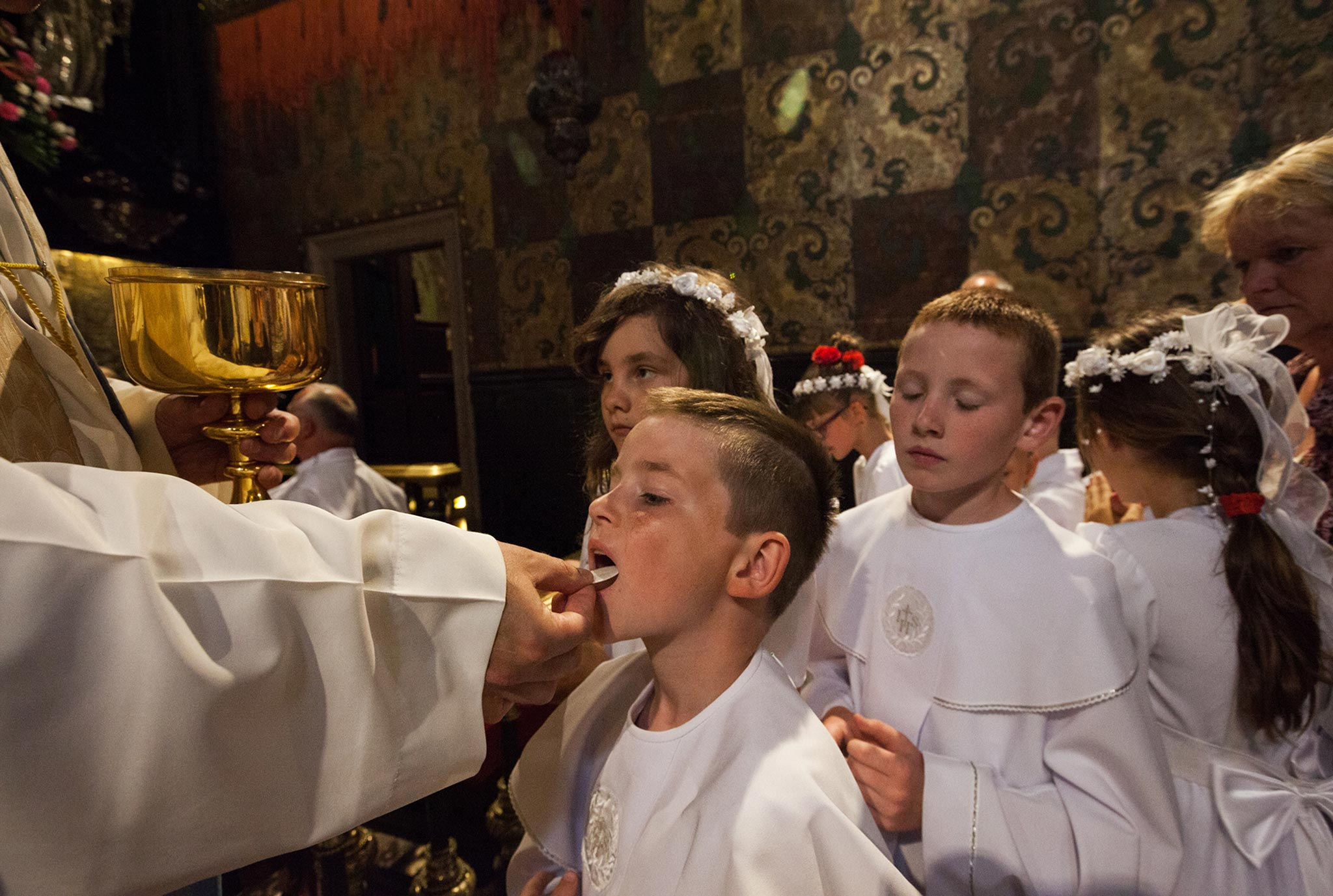 A boy receives Communion at the Jasna Góra Monastery, in Częstochowa, Poland. The Black Madonna—a revered painting of a dark-skinned Virgin Mary and Child Jesus, said to be the work of St. Luke—is housed in this sanctuary.