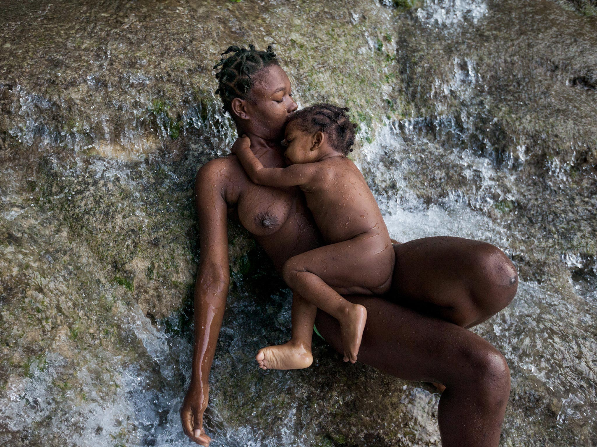 A mother and daughter in Ville Bonheur, Haiti, bathe in the sacred Saut d'Eau falls. Ezili Dantò is said to have appeared on a palm tree here in 1849. Father Johann Roten, a Marian scholar, says Mary's presence in the Caribbean can be traced to the merging of two cultures—Spanish Catholics and pre-Christian Africans—that began in the early 1500s.