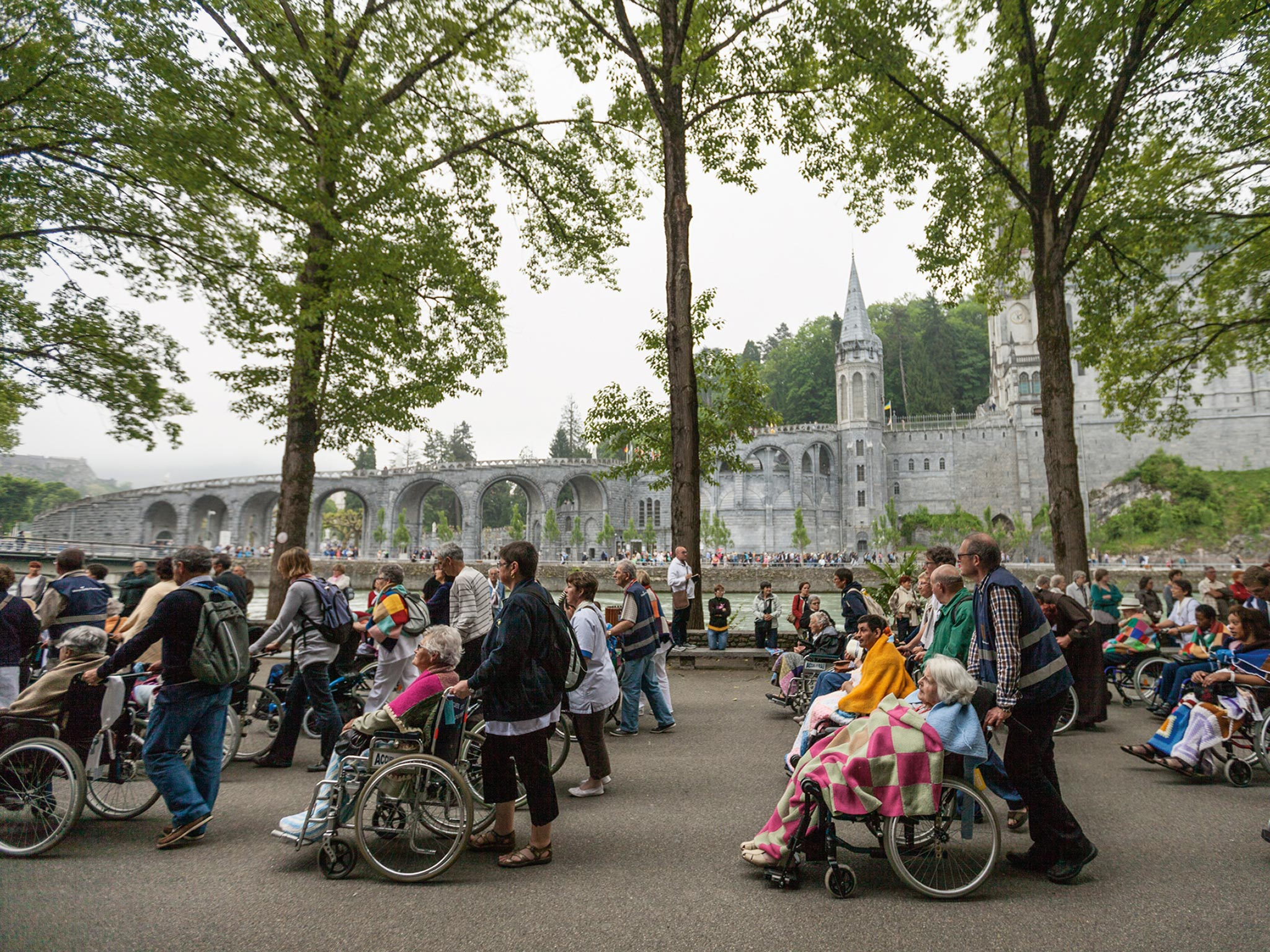 In Lourdes, a small town in France with an outsize reputation for miracles and Marian signs, volunteers push the wheelchairs of terminally or chronically ill pilgrims. Some 80,000 sick or disabled devotees a year seek a cure at the shrine of Mary.