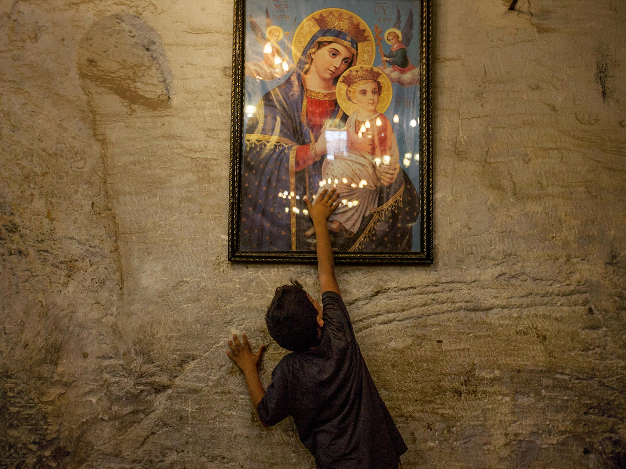 """A young boy in the Deir al Adra monastery reaches up to touch a painted image of Mary. In the Koran, Maryam (Mary) is the holiest woman mentioned. """"So the Virgin Mary is not at all strange to Muslims,"""" says Roten. """"In fact, wherever there is a connection between Christians and Muslims—or any two groups that know and love her—there is a common value in the covenant mother."""""""
