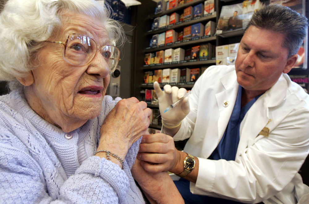 ** FILE ** Frances Welch, 95, rolls up her sleeve in preparation for a flu shot from registered nurse Randy Kortness at a flu shot clinic hosted by a grocery store in Seattle, in this Dec. 7, 2004 file photo. A new study based on more than three decades of U.S. data suggests that giving flu shots to the elderly has not saved any lives. (AP Photo/Elaine Thompson, File)