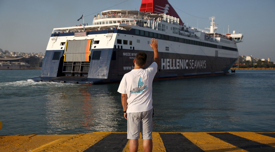 A man waves goodbye as a ship departs from the port of Piraeus, Greece © Yiannis Kourtoglou / Reuters