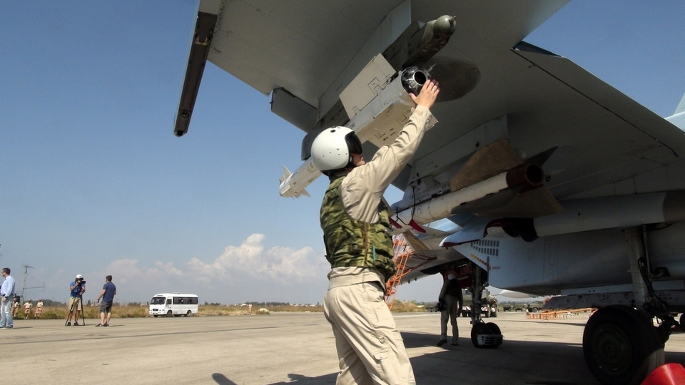 A Russian pilot checks an air-to-air missile on his Su-30 jet fighter before taking off at Hmeimim airbase in Syria, Oct. 5, 2015.  AP