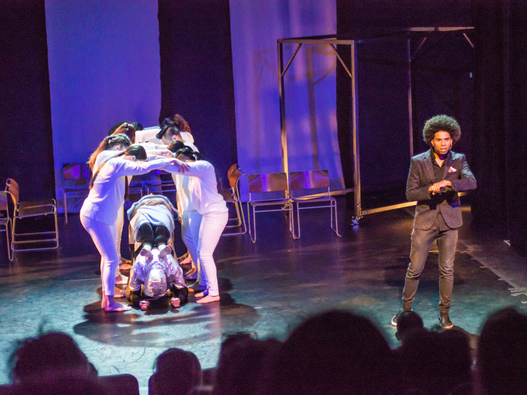 """Group of EPIK Dancers assemble together to create an arch over """"Kat"""" to symbolize an MRI machine."""