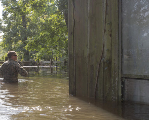 West Orange, Texas - WEST ORANGE, Texas – U.S. Marine Corps Sgt. Austin Rusk a reconnaissance Marine team leader with Charlie Company, 4th Reconnaissance Battalion, 4th Marine Division, Marine Forces Reserve, wades through waist deep flood water in order to get to a second story door to complete an emergency rescue call in West Orange, Texas, Sept. 1, 2017. Marine Corps Reserve forces are supporting FEMA and state and local officials, focused on life-saving efforts and resupply missions in the aftermath of Hurricane Harvey. (U.S. Marine Corps photo by Pfc. Samantha Schwoch/Released)