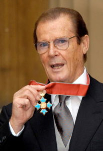 Sir Roger Moore receiving his Knighthood for charitable services at Buckingham Palace on October 8, 2003. (Photo by Anwar Hussein/WireImage)