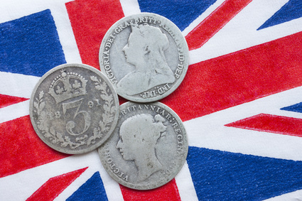 Three Queen Victoria silver threepences from the 19th century (from 1873, 1891, 1898) on a British flag. Concept representing history of the British Empire, Victorian time or old coin collecting.
