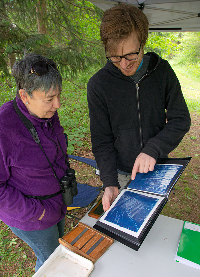 Artist in residence Andrew Musil showing a visitor examples of cyanotype images he's made on site