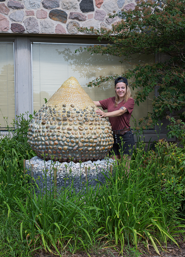 The artist, a young woman, with her tear-drop shaped sculpture, entitled Geo Egg