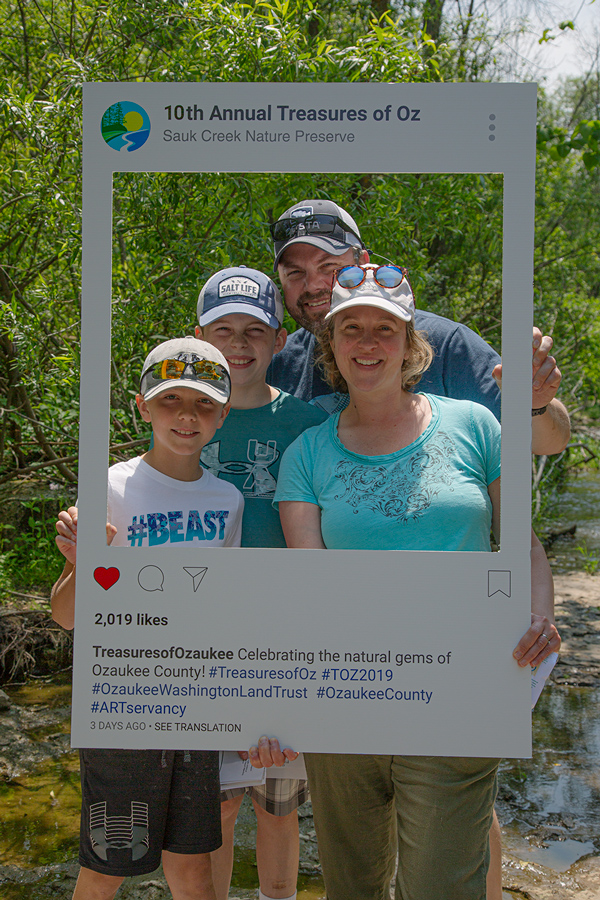 family of four in Instagram frame posing for a selfie at the creek