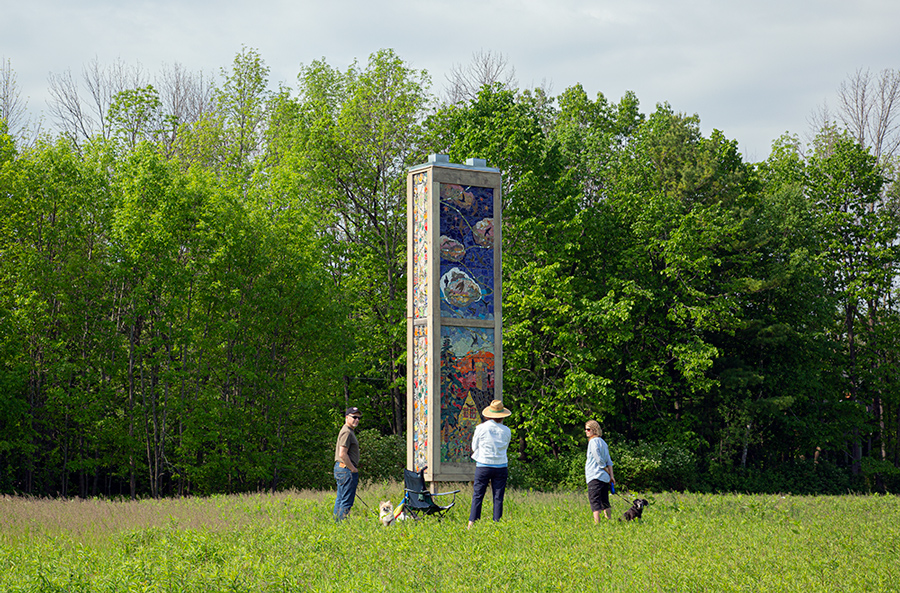 three people with dogs in front of swift tower art installation