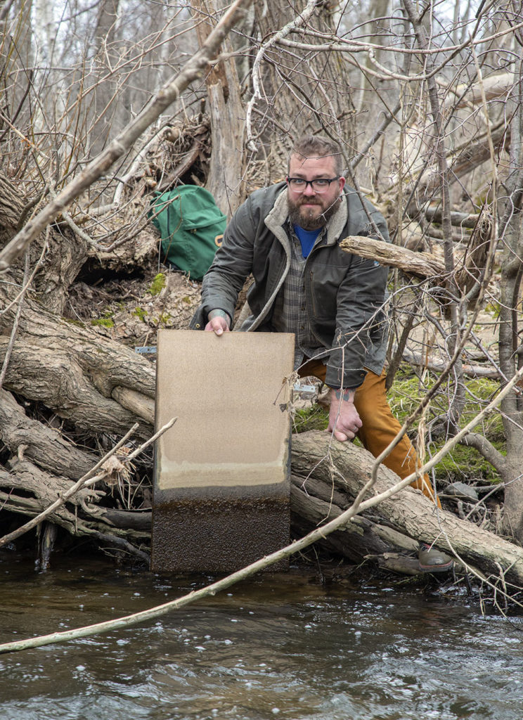 The artist removing a canvas from Sauk Creek.