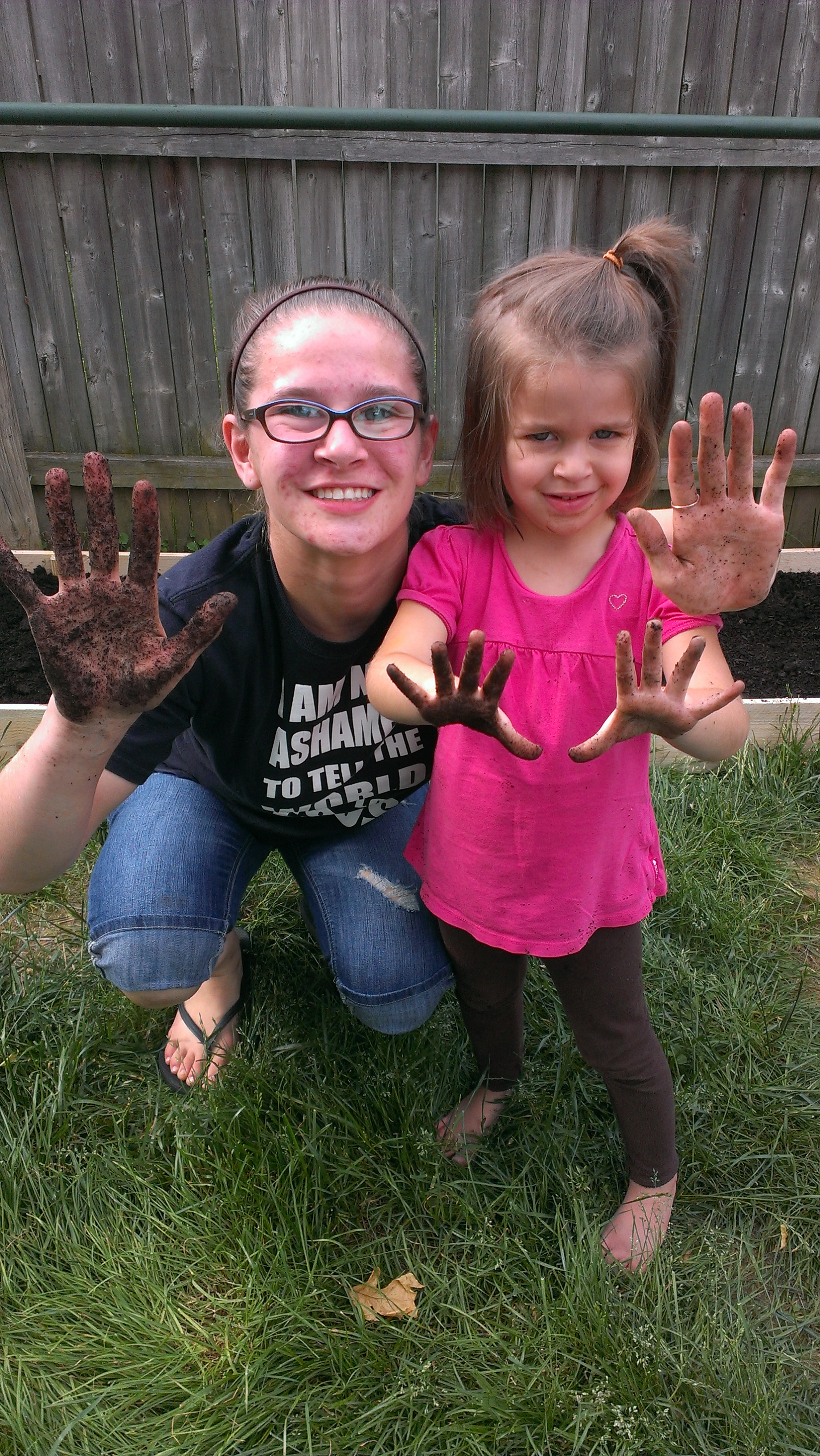 Two girls with dirty hands   DIY Raissed Garden Bed   Making the Most Blog