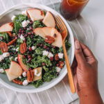 Kale Apple Salad in a white bowl with Pomegranate Dressing