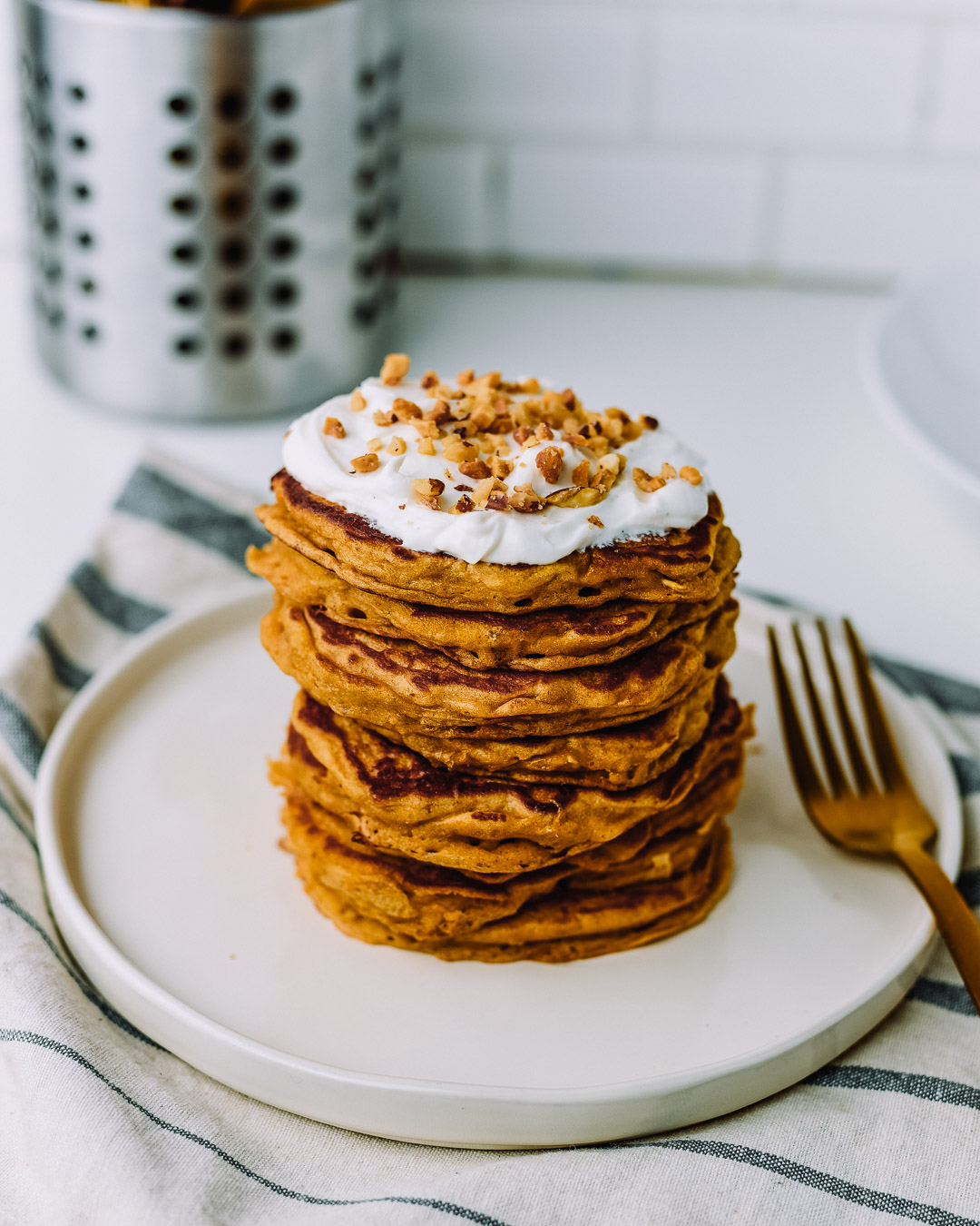 Stack of oatmeal pancakes topped with vanilla skyr and chopped peanuts on a white plate sitting on top of a kitchen towel on a white table.