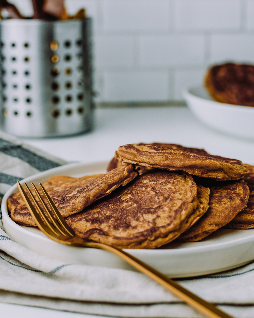 Oatmeal pancakes on a white plate with a fork, sitting on top of a kitchen towel on a white table.