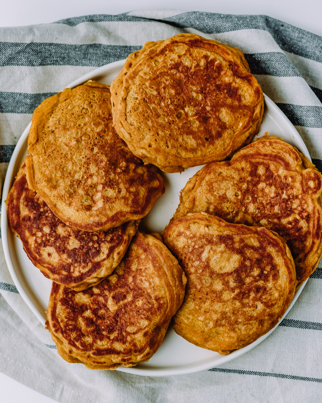 Stack of oatmeal pancakes on a white plate sitting on top of a kitchen towel on a white table.