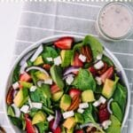 Bowl filled with strawberries, spinach, avocado, on a grey and white kitchen towel
