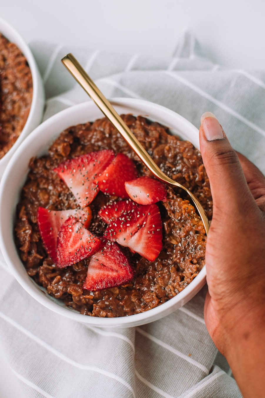Hand holding a thick of bowl of chocolate oatmeal with strawberries and chia seeds.