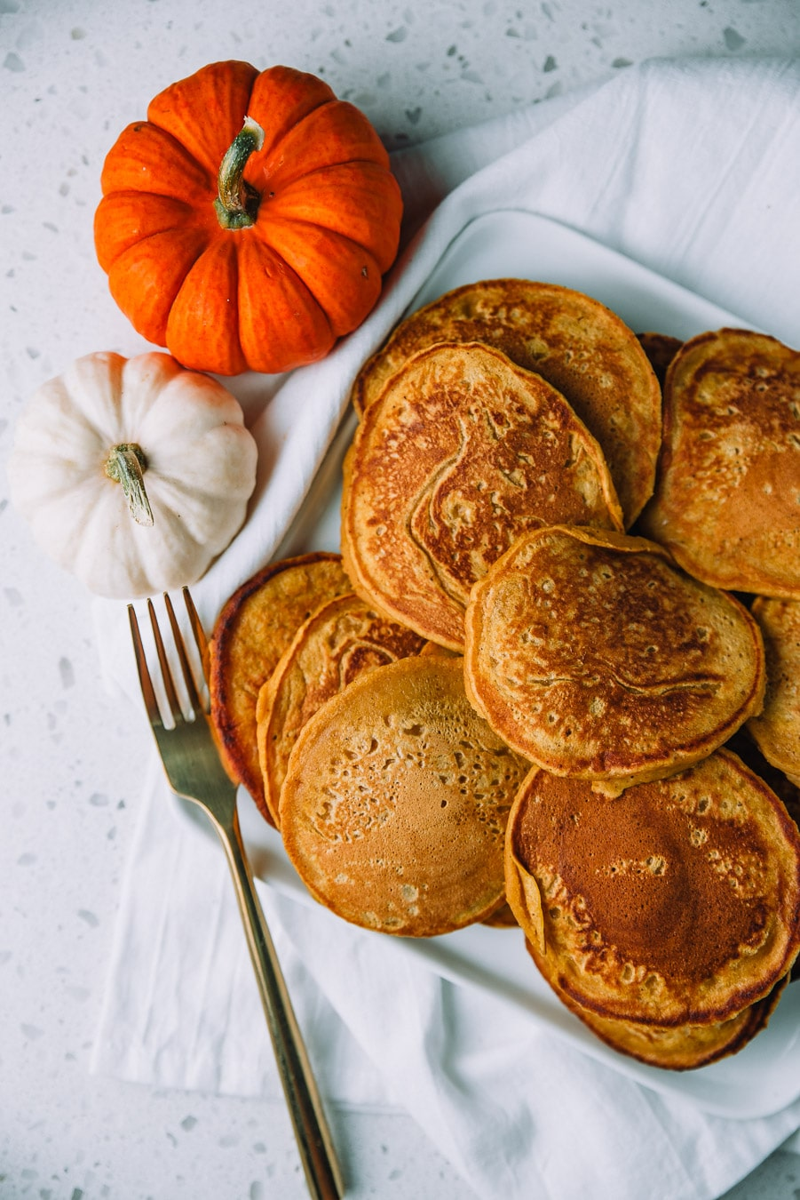 Easy Pumpkin Pancakes piled on a square plate placed on a white napkin on a countertop
