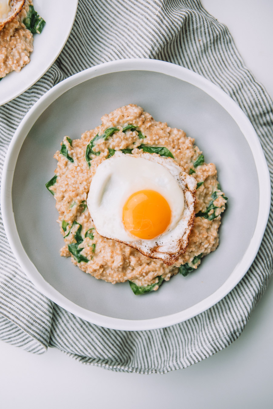 Bowl of Savory Spinach Oatmeal with Fried Eggs