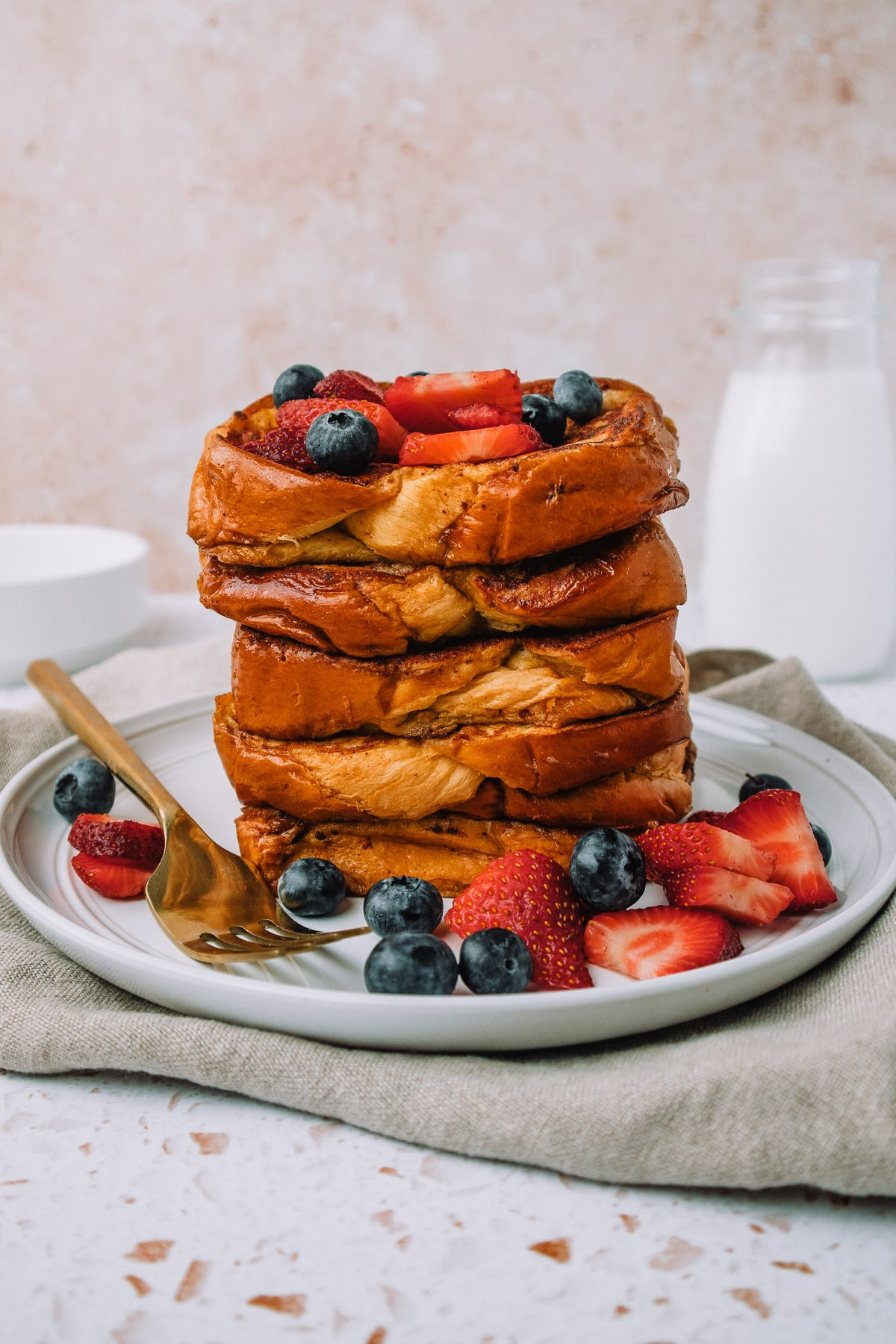 Delicious slices of brioche french toast stacked on a plate with fresh strawberries and blueberries for a yummy breakfast or brunch