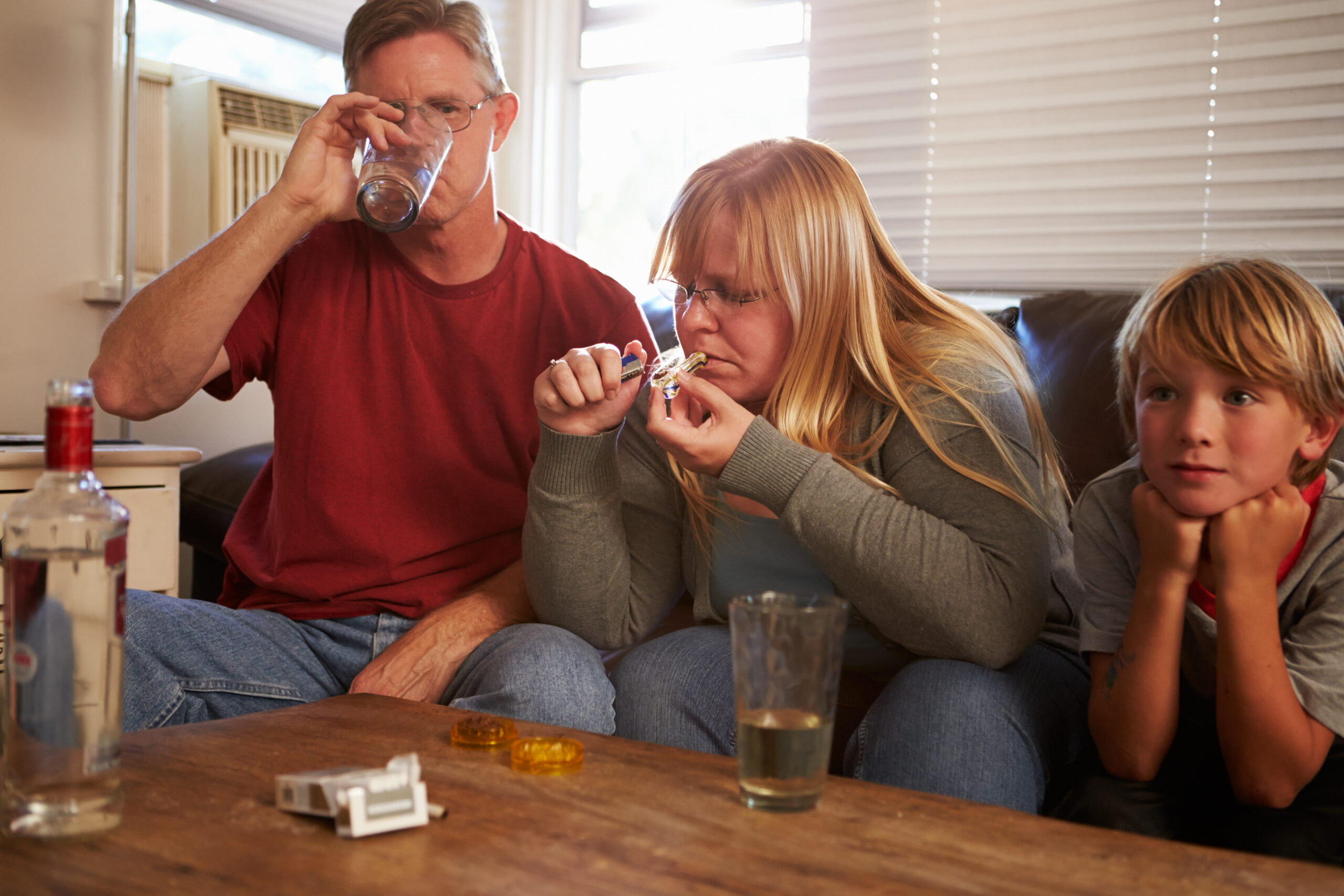 Parents,Sit,On,Sofa,With,Children,Taking,Drugs,And,Drinking