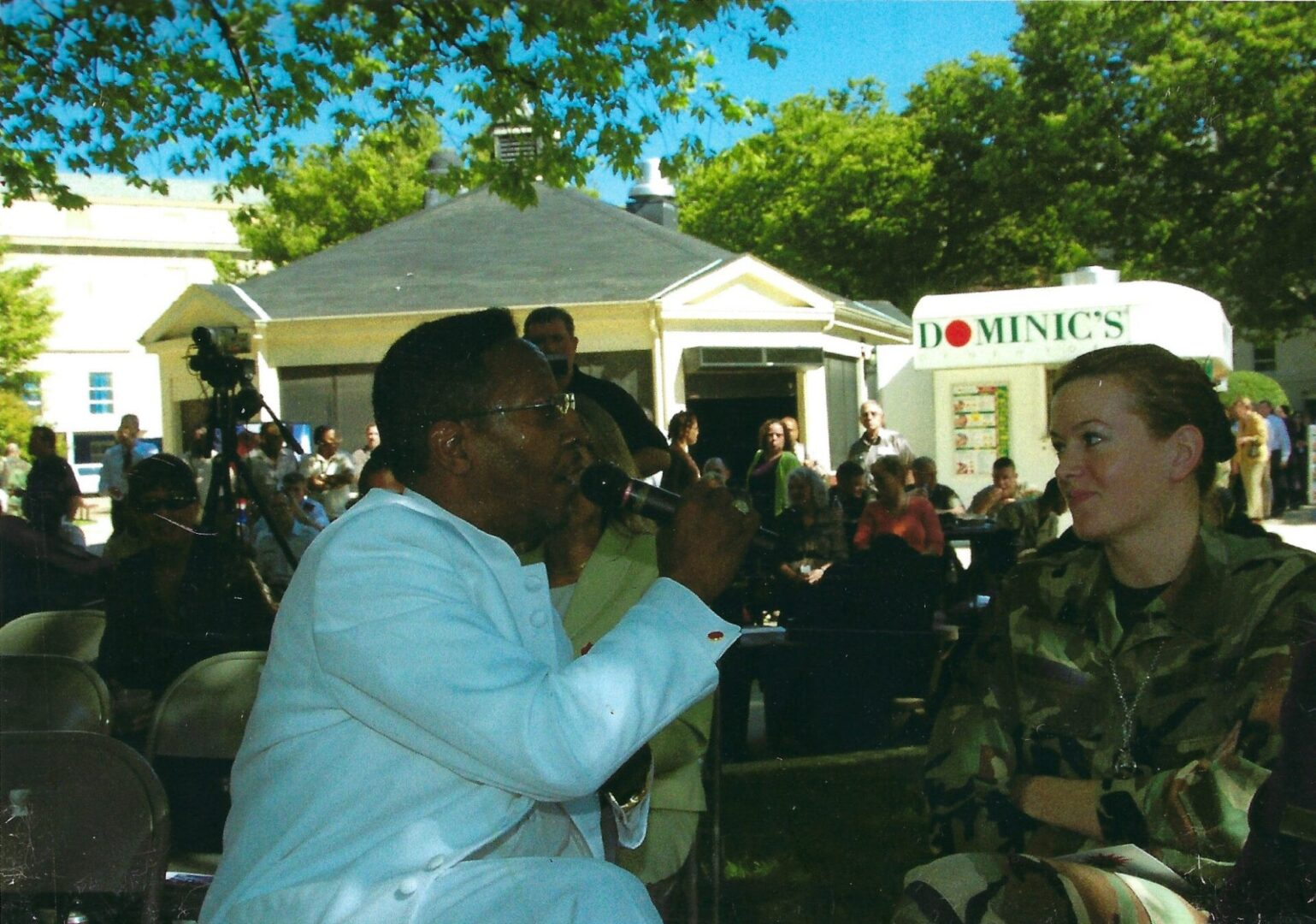 a man in white singing to a female soldier