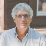 Man with glasses, dark hair and grey shirt in light background. Guest of new episode titled Awake and Aware: The Science of Becoming a Better Human and Society with Stuart Shanker & Jim Davies PhD