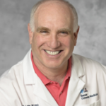 man with white medical jacket and pink shirt, guest of episode about change of attitude and enduring with Richard Lane MD, Ph.D., Gay Hendricks, & Carol Kline