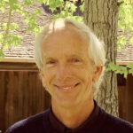 man with white hair and black shirt, guest of new episode of positive psychology podcast Harvesting Happiness Talk Radio with Wendie Colter, Professor Paul J. Mills, & Reverend Tiffany Barsotti about medicine and divine insight