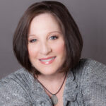 woman with short dark hair and gray shirt, guest of new episode of positive psychology podcast Harvesting Happiness Talk Radio with Wendie Colter, Professor Paul J. Mills, & Reverend Tiffany Barsotti about medicine and divine insight