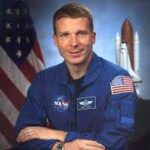 Man with blue NASA uniform and united states flag,guest of new episode of positive psychology podcast Harvesting Happiness with Heino Falke & Terry Virts about exploring heavenly destinations