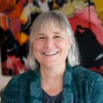 woman with gray hair and colorful background with blue shirt, guest of positive psychology podcast Harvesting Happiness in the new episode called  Life Transformation and Energy Activation with Sarah Peyton & Melanie Dean