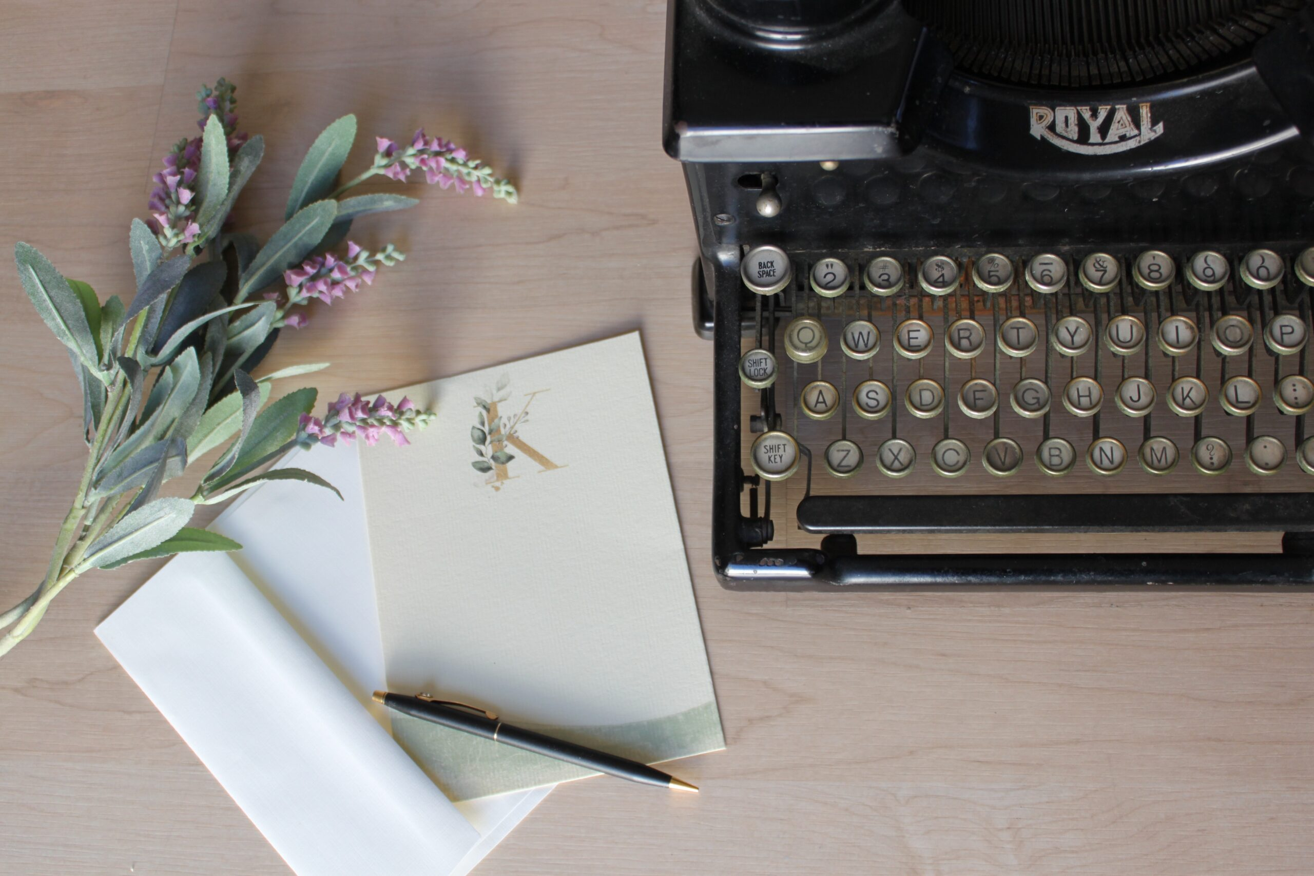 Typewriter with flowers, paper and pencil on a wooden desk.