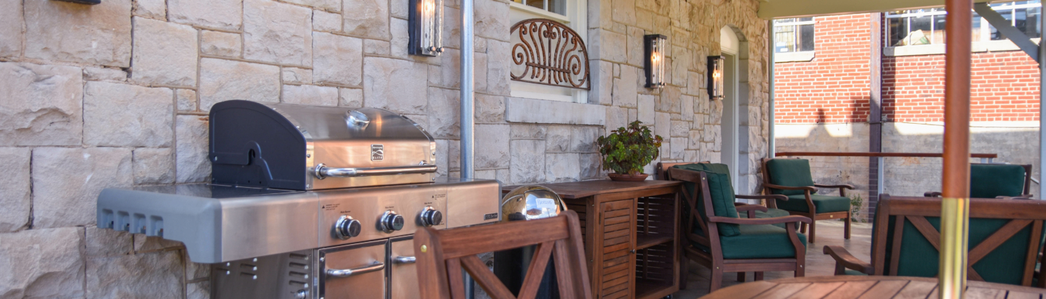 a grill and tables on the back porch of the Stone House