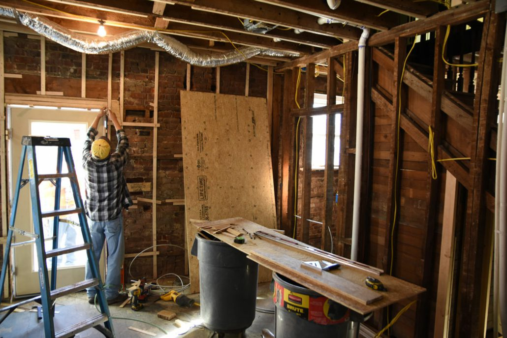 worker restores interior walls of the Stone House