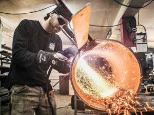 a man welding a cylndrical piece of metal
