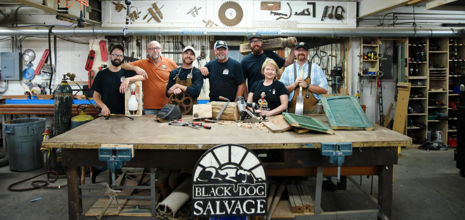 Salvage Dawgs crew stand behind a work bench in the Black Dog Salvage shop