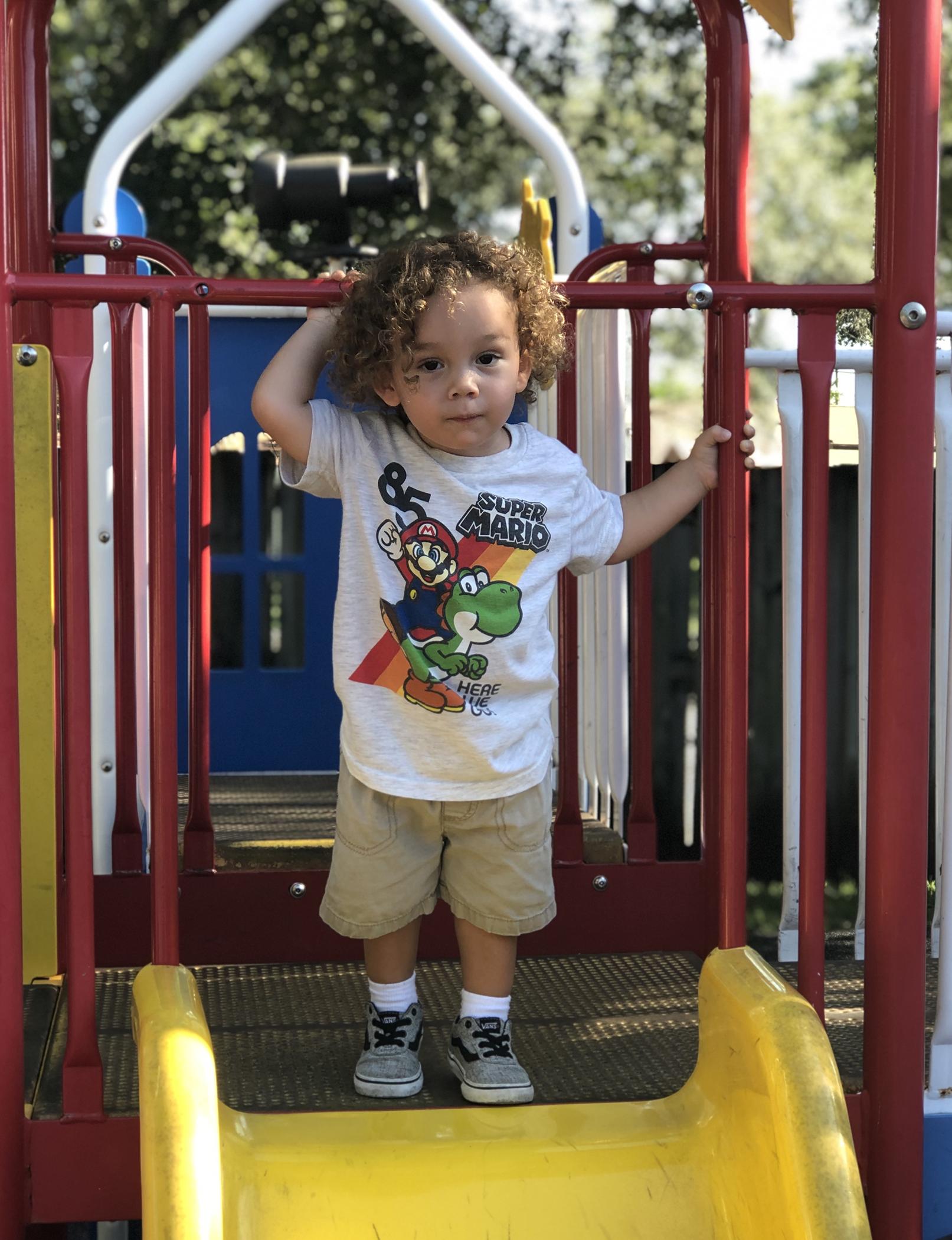 holycross-kid-standing-at-top-of-playground-slide
