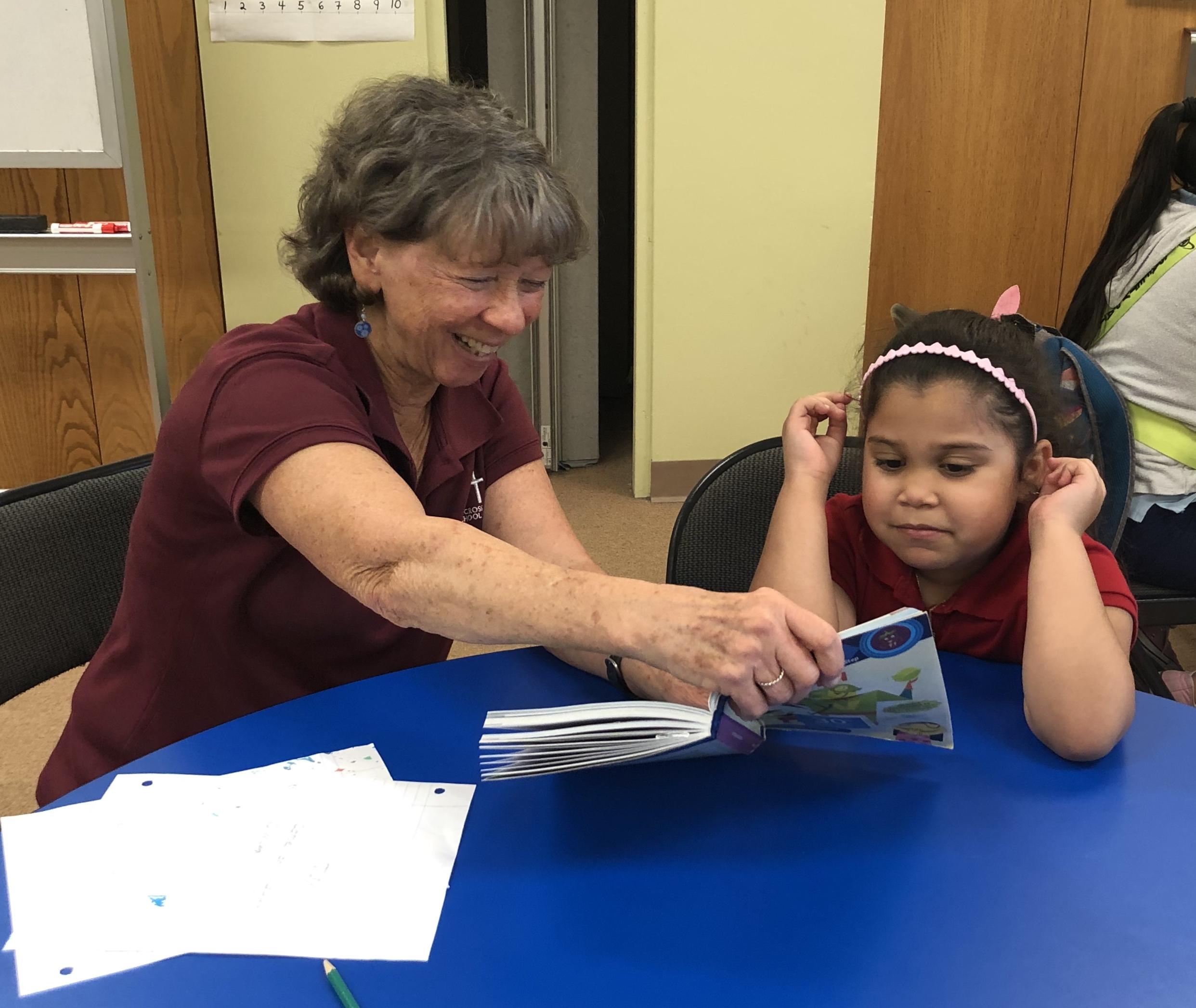 holycross-teacher-helping-girl-to-read