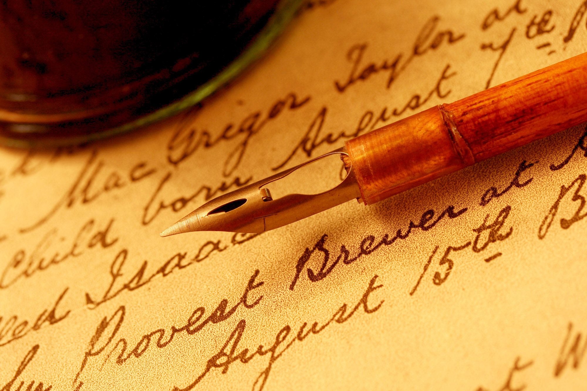 Vintage wooden-handled nib pen and inkwell, on a page of 18th century script.
