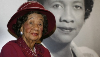 """** HOLD FOR RELEASE UNTIL 12:01 a.m. EDT TUESDAY JUNE 15, 2010 **  FILE - In this Feb. 14, 2008, file photo Dorothy Irene Height, longtime president of the National Council of Negro Women the leading female voice of the 1960s civil rights movement, poses in front of her portrait inside the """"Freedom's Sisters"""" exhibition at the Cincinnati Museum Center, in Cincinnati, wearing her signature-style Bene' hat. Most of the hats worn by Height were created by Washington milliner Vanilla Beane, and became known far and wide as a statement of her dignity and grace.  (AP Photo/David Kohl, File)"""