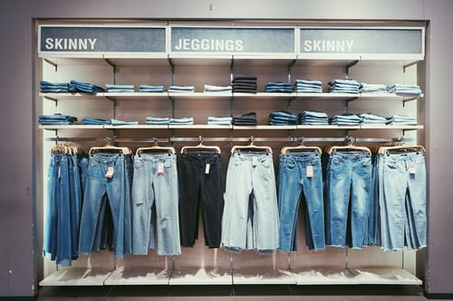 jeans hanging in store as feature image for apparel industry blog