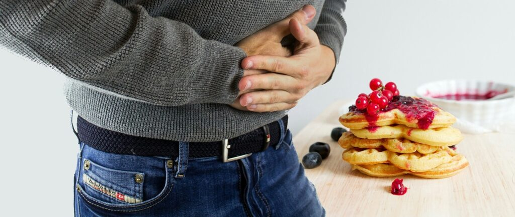 man holding stomach and large plate of food