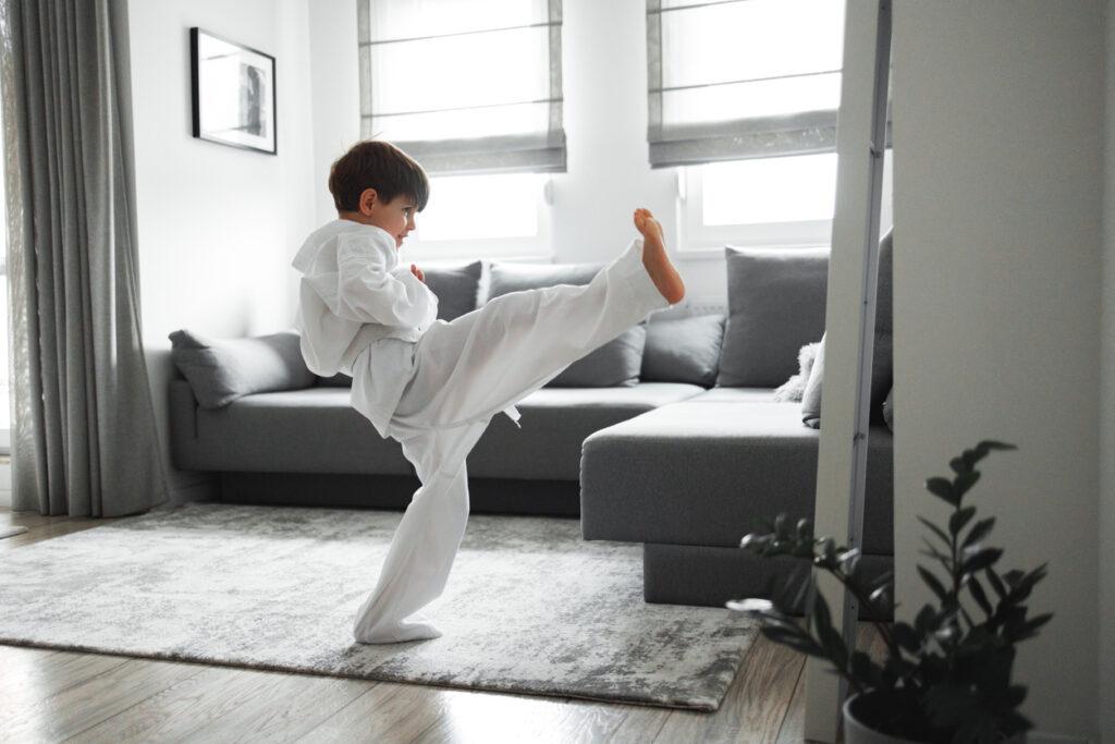 7 years old boy dressed in kimono, training taekwondo at home.